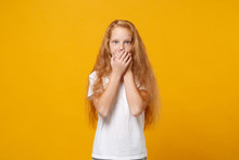 Wall Mural - Shocked little ginger kid girl 12-13 years old wearing white t-shirt isolated on yellow background children studio portrait. Childhood lifestyle concept. Mock up copy space. Covering mouth with hands.