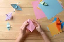 Wall Mural - Young woman making origami on wooden table