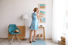 Wall Mural - Female interior designer decorating white wall with pictures indoors