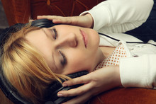 Wall Mural - Blonde girl on sofa listening to music with headphones