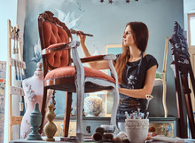 Wall Mural - Female artist painting vintage chair in white color with paintbrush in workshop.