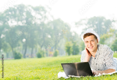 Wall Mural - young man working in the park with a laptop