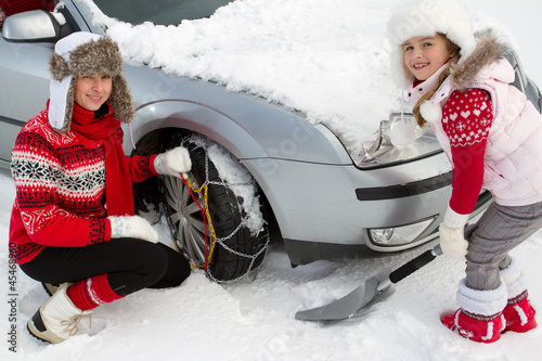 Wall Mural - Winter, family putting snow chains onto tyre of car
