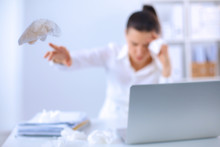 Wall Mural - Stressed businesswoman sitting at desk in the office