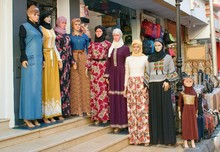 Wall Mural - Female mannequins wearing modern arabic muslim dresses and hijabs exhibited on the street