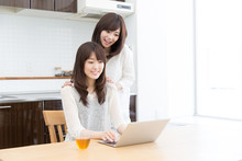 Wall Mural - asian women using laptop in the kitchen