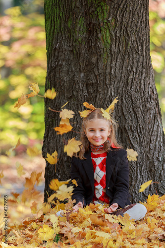 Wall Mural - Autumn fun - girl playing in autumn park