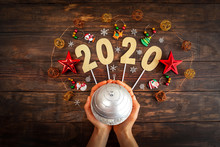 Wall Mural - New year 2020 concept with Christmas decorations and female hands holding silver bauble against wooden background - top view