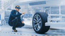 Wall Mural - Automotive Engineer Working on Electric Car Chassis Platform, Using Augmented Reality Headset. In Innovation Laboratory Facility Concept Vehicle Frame Includes Wheels, Suspension, Engine and Battery.