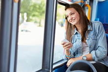 Wall Mural - Teenage Girl Wearing Earphones Listening To Music On Bus