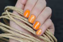 Wall Mural - Beautiful female hand with orange nail design.