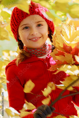 Wall Mural - Autumn fun - girl playing in autumn leaves