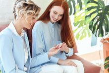 Wall Mural - Happy Two beautiful ladies in blue clothes sit on sofa and discuss manicure. Fresh background greens, plants. Redhead woman.