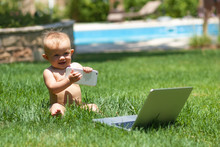 Wall Mural - Cute baby  playing with laptop outdoors on green grass