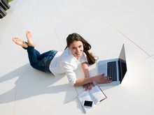 Wall Mural - relaxed young woman at home working on laptop