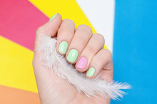 Wall Mural - Beautiful female hand with light green and pink nail design.