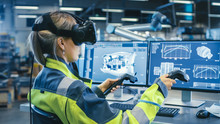 Wall Mural - Factory: Female Industrial Engineer Wearing Virtual Reality Headset and Holding Controllers, She Uses VR technology for Industrial Design, Development and Prototyping in CAD Software.
