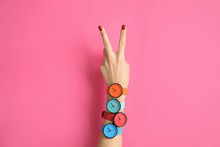 Wall Mural - Woman with many bright wrist watches on color background, closeup. Fashion accessory