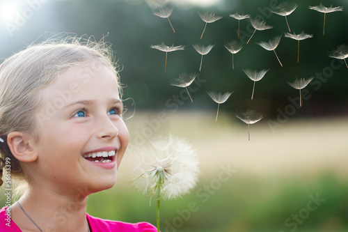 Wall Mural - Summer joy - lovely girl blowing dandelion