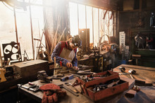 Wall Mural - A female craftsman in her workshop working on a metal piece