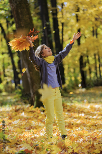 Wall Mural - Autumn fun - lovely girl has a fun in autumn park
