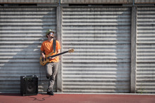 Wall Mural - Young musician playing bass guitar