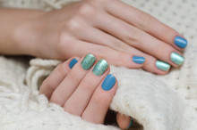 Wall Mural - Beautiful female hand with blue and green glitter nail design.