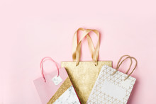 Wall Mural - Paper shopping bags on pink background. Holiday sale concept in pastel colors
