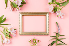 Wall Mural - Golden photo frame with flowers on pastel pink background. Hello Spring greeting card