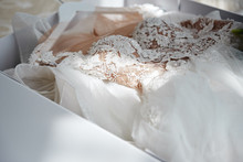 Wall Mural - Beautiful luxury wedding dress in white box on bed, copy space. Bridal morning preparations. Wedding concept